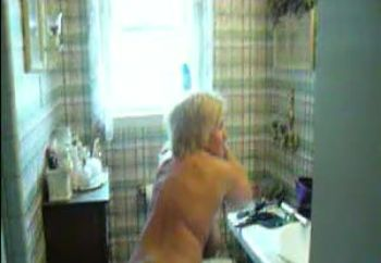 Blow drying her hair--nude