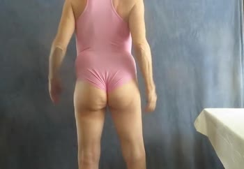 Male bitch poses in a pink leotard.